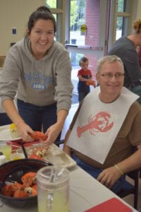 Maine Veterans' Homes resident enjoys a lobster wit assistance from a staff member
