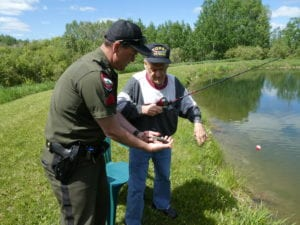 MVH Caribou resident fishes with a member of Maine Inland Fisheries and Wildlife
