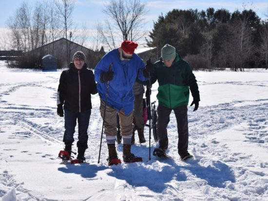 A Maine Veterans' Homes resident is assisted while snowshoing