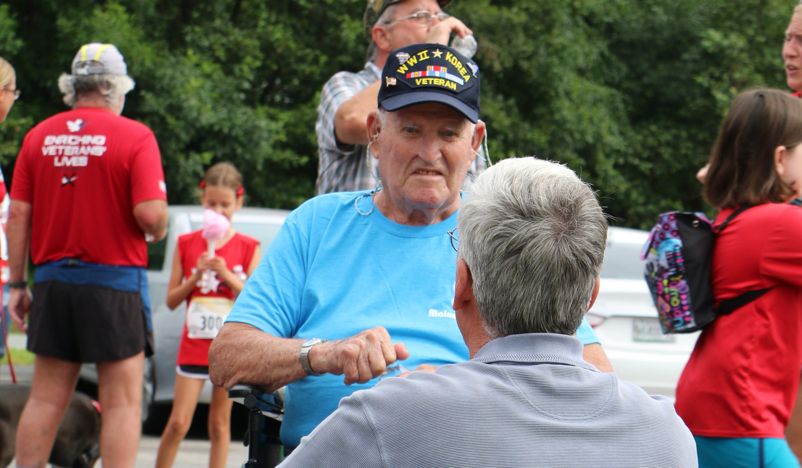 A Maine Veterans' Homes resident talks to family at an outdoor event