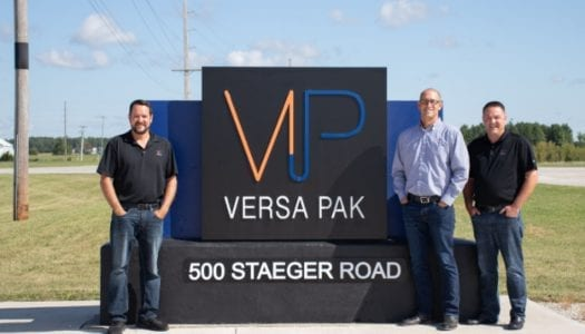 Versa pak employees standing in front of versa pak sign