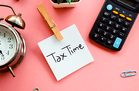Tax time reminder sticky note with calculator and clock.