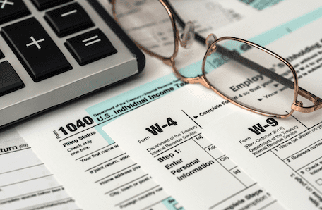 Tax forms, eyeglasses, and calculator