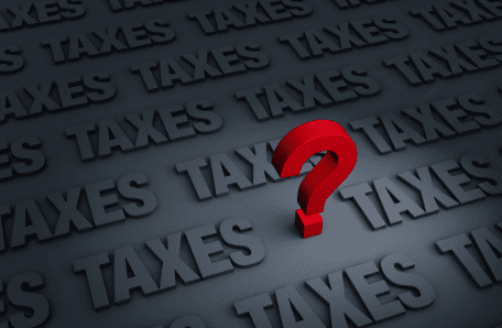 "Dark background with the word ""taxes"" and question mark"