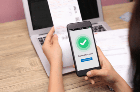 Person checking phone while looking at paper receipt in front of computer