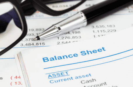 """Paper labeled """"Balance Sheet"""" with eyeglasses and pen on top"""