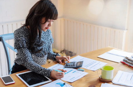 Young woman working with paperwork on budget and finances.