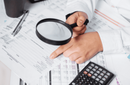 Person using magnifying glass to look at financial documents