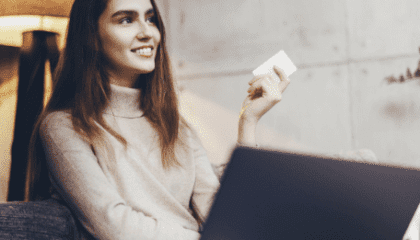 Woman holding a bank card while sitting on a couch with her computer