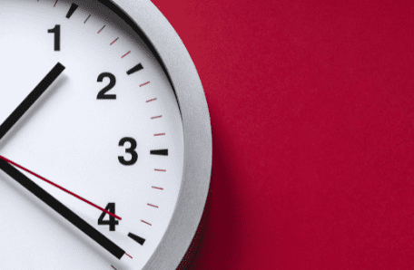 Clock showing hour, minute and second hand on red background
