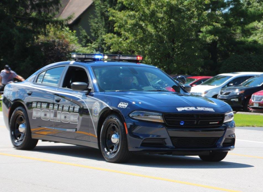 New Bremen police car driving down street with lights on and window down