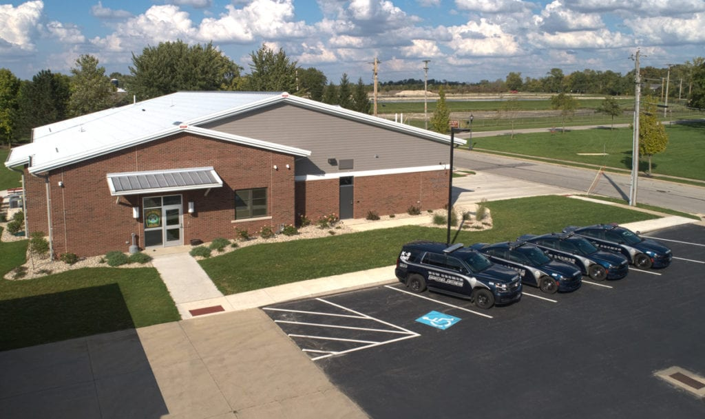 Higher shot of four New Bremen police cruisers parked in front of police department