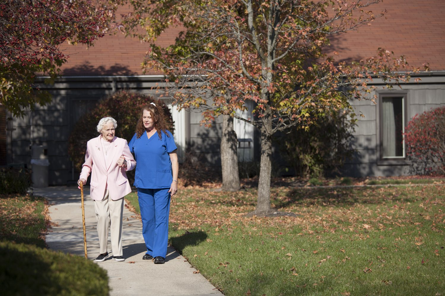 A senior resident at an assisted living and long term care resident walks outside with the help of a staff member