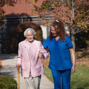 A considerate staff member helps a senior woman walk outside at a rehab and nursing center
