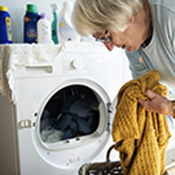 Senior woman loads laundry into the washer