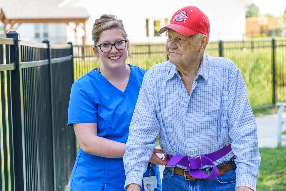 A senior man walks with the help of a staff member outside at the Canal Winchester nursing and rehab center