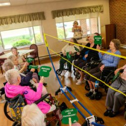 Long-term care residents play a game with balloons and fans at Pickaway Manor