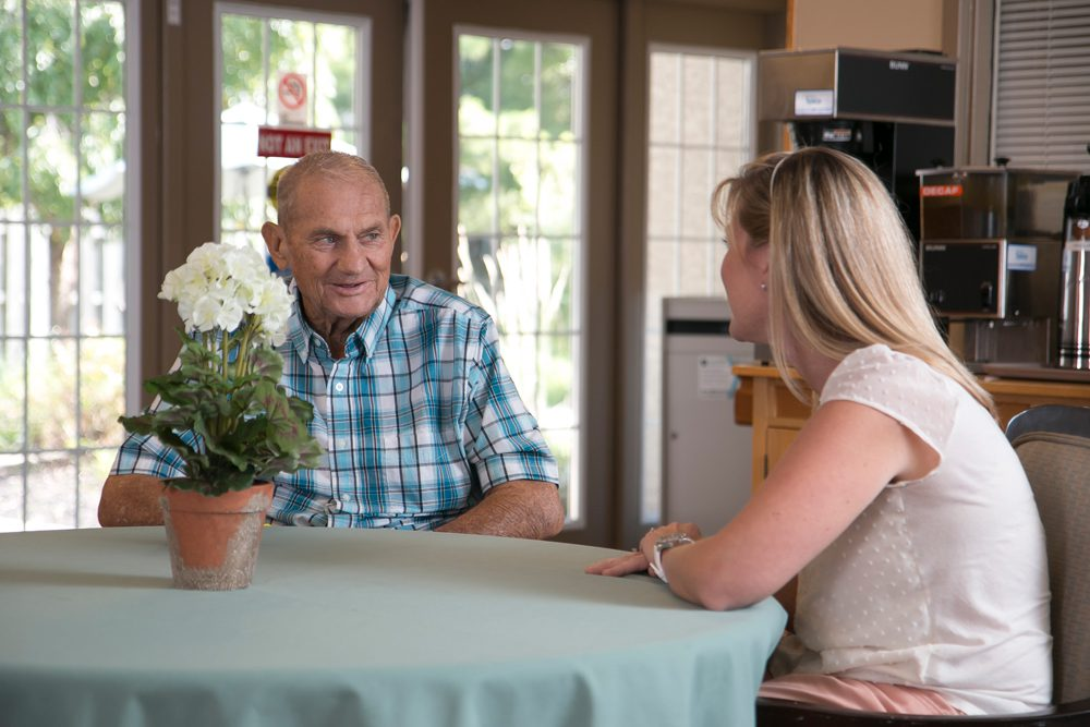 A senior man speaks with a visitor at an assisted living and long term care community