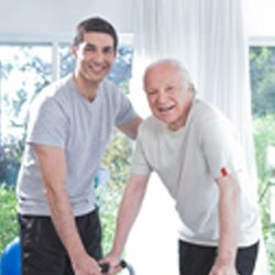 A physical therapist helps a senior man with his walker