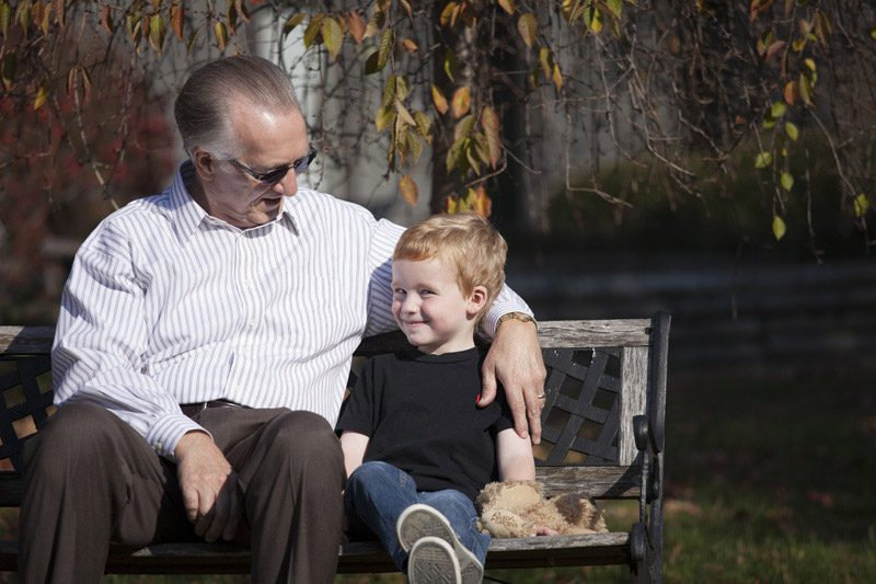 Senior man sits with grandchild on a bench outside of Whetstone Rehabilitation Center, Skilled Nursing & Assisted Living