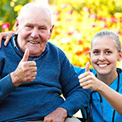 Senior man gives thumbs up with rehab and nursing center employee