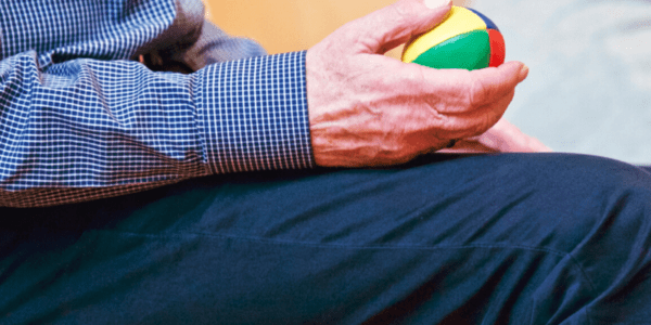 Older man holding small ball during therapy