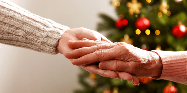 Senior adult and daughter holding hands by christmas tree
