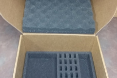 Cardboard box with grey foam inserts