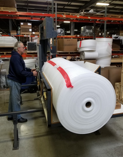 Man working in warehouse with giant roll of foam